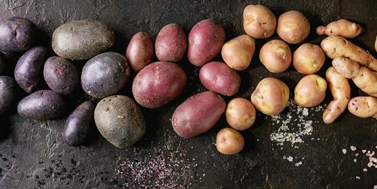 Different kinds of potatoes on a black table
