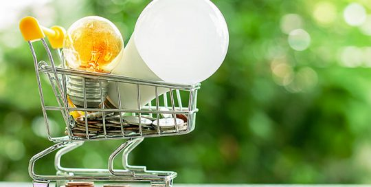 Small cart with two light bulbs and spare change ona table against a green scenery background