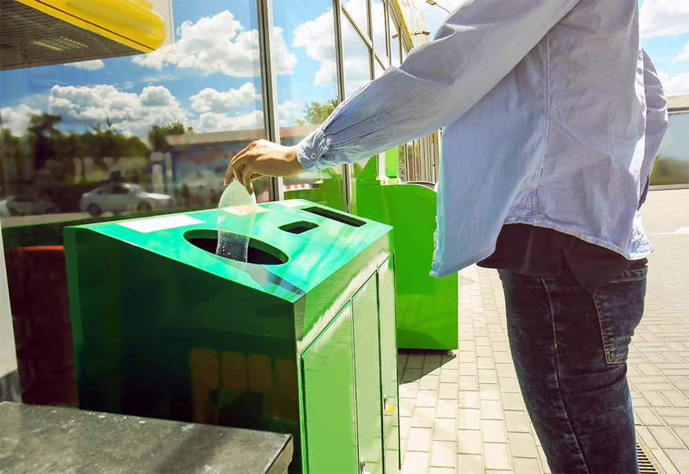 Person throwing away a plastic bottle in a garbage can outside of a store